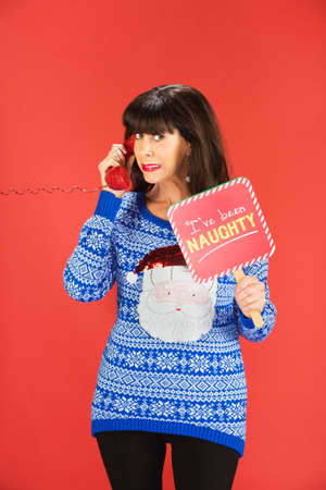 Ashamed adult woman in ugly blue sweater with naughty sign on phone Imagens