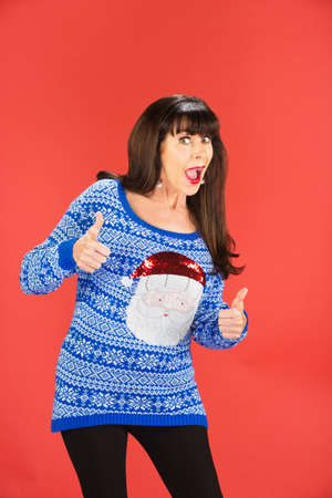 Excited single woman in tacky Christmas sweater with thumbs up over red background 版權商用圖片 - 69218515