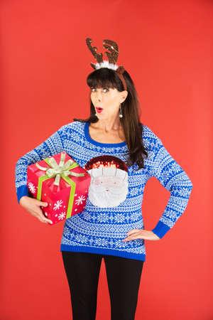 flattered: Excited beautiful single woman in tacky knitted sweater and antlers tiara holding a large Christmas gift