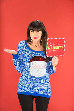 bashful: Woman in blue Santa Claus sweater holding naughty sign with confused expression