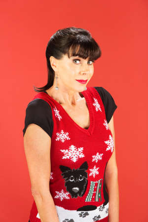 Front view on grinning woman wearing ugly Christmas sweater over red background Imagens - 69218522