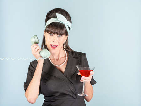 Pretty retro woman in black dress with Cosmopolitan cocktail and phone receiver