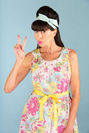 puckered lips: Single 1950s era woman in sleeveless dress gesturing a V symbol with her fingers