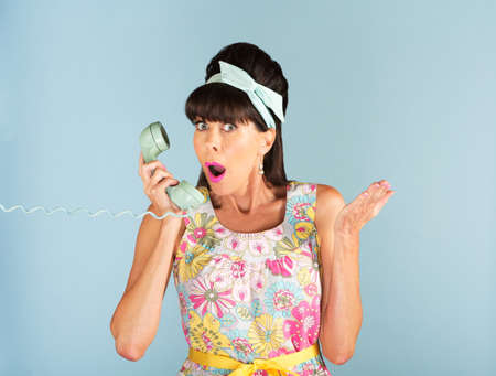 Single Caucasian woman in 1950s style sleeveless dress with surprised expression while holding phone over blue background Stock Photo