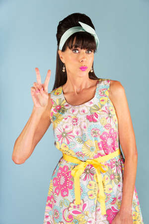 puckered lips: Cute 1950s era woman in dress with floral patterned dress gesturing a V symbol with her fingers