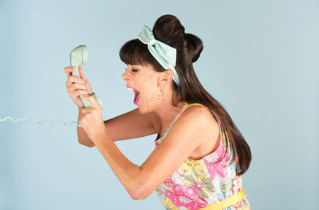 Angry woman in flowery dress yelling into a telephone over blue background Stock Photo