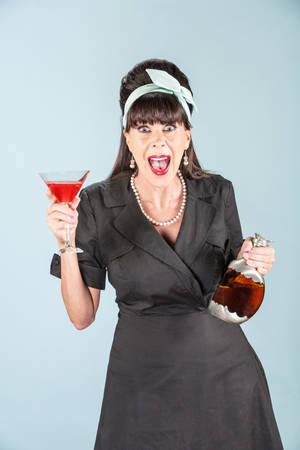 agape: Screaming retro woman in black dress with Cosmopolitan and decanter Stock Photo