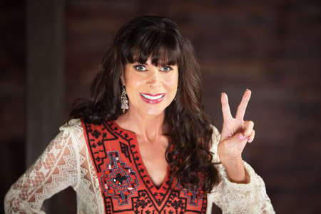 Smiling adult woman in ornate red blouse making a V gesture with two fingers