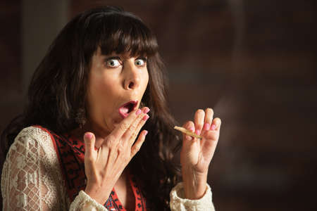 Embarrassed female smoker holding a marijuana cigarette while coughing
