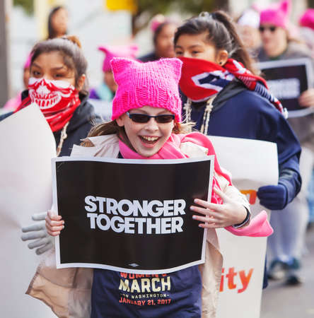 TUCSON, AZ - JANUARY 21: Happy trio of white and Latina girls holding protest signs at Womens March on Washington January 21, 2017 in Tucson, AZ, USA. Editorial