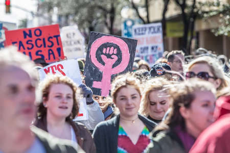 mar: TUCSON, AZ - JANUARY 21: Selective focus view of woman holding pink female with fist sign at the Womens March on Washington January 21, 2017 in Tucson, AZ, USA.