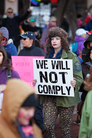 dissent: TUCSON, AZ - JANUARY 21: Tall woman holding sign of defiance at the Womens March on Washington protest January 21, 2017 in Tucson, AZ, USA.