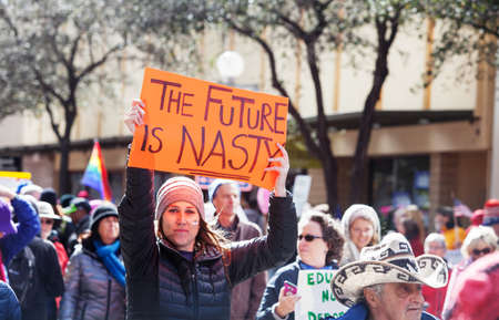 dissent: TUCSON, AZ - JANUARY 21: Adult female in hat holding The Future Is Nasty protest poster during the Womens March on Washington January 21, 2017 in Tucson, AZ, USA.