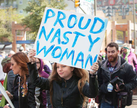 protestor: TUCSON, AZ - JANUARY 21: Female protestor holding a Proud Nasty Woman poster at the Womens March on Washington January 21, 2017 in Tucson, AZ, USA.