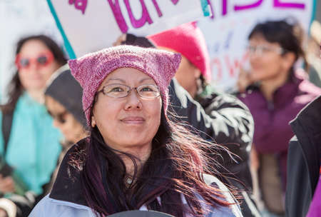 TUCSON, AZ - JANUARY 21: Grinning woman in eyeglasses with pink pussy hat celebrating the Womens March on Washington January 21, 2017 in Tucson, AZ, USA.