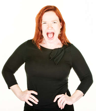 Yelling red haired Caucasian woman in tight fitting blouse with hands on hips Stock Photo
