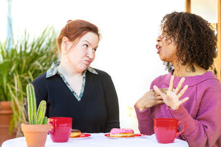 puckered: Woman with doubtful expression listening to friend talking at table