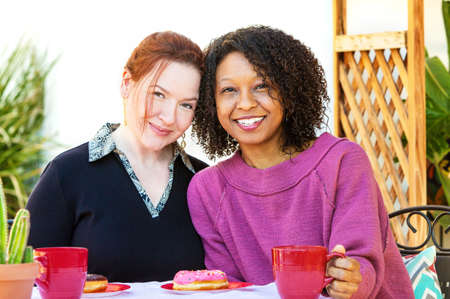 Happy adult mixed lesbian couple sitting together at table with coffee and donuts