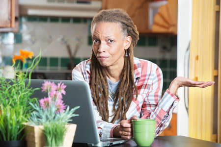 Single unimpressed woman in kitchen with computer and coffee with palm up Stock Photo