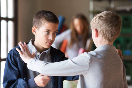 Black and white teenage male students fighting indoors. Obscured teacher in background.