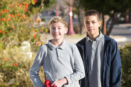 Pair of teen male students standing outside during spring season Stock Photo