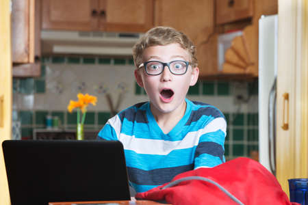 Cute teen boy in eyeglasses with laptop and surprised expression