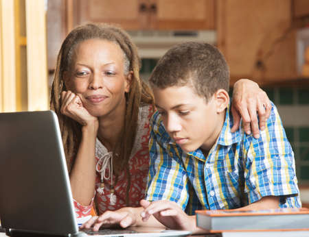 Mother overlooks as her teenaged son uses his laptop to study in their kitchen Stock Photo