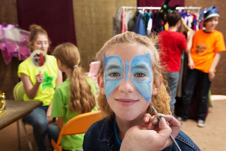 Close up view of girl getting her face painted while seated in a dressing room Foto de archivo