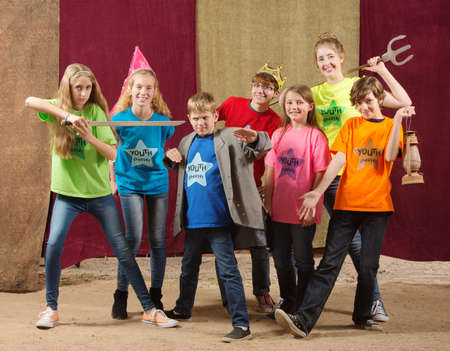 Children at acting camp pose together with swords and trident Standard-Bild
