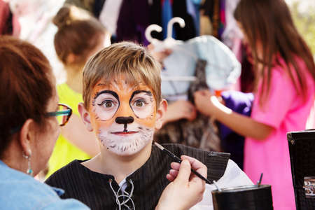 Teacher paints face of young actor to resemble a tiger as he prepares for  production Stock fotó