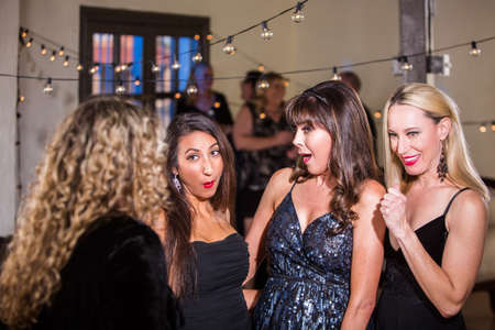 Four shocked women sharing gossip or joke at a party Stock Photo