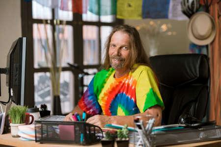 Smiling man in tie dye shirt at his desk