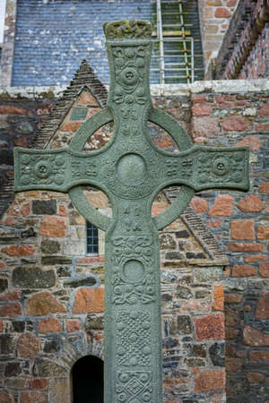 Saint Johns High Cross in front of historic Iona Abbey vertical shot