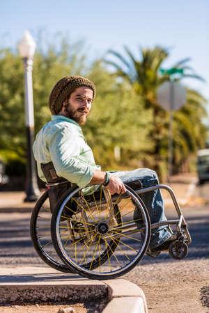 Young man in wheelchair rolls off high city curb Standard-Bild - 120888107