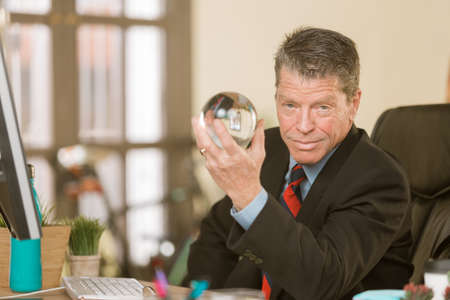Confident professional man with a crystal ball Standard-Bild - 120888109