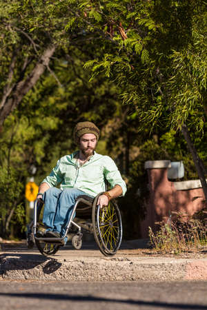 Young man in wheelchair negotiates high city curb Standard-Bild - 120888115