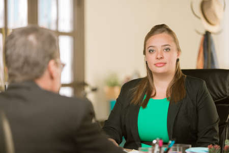 Happy young professional woman in her office with colleague Standard-Bild - 120888251