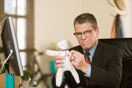 Angry professional man putting a pin into the heart of a Voodoo doll Standard-Bild - 120888015