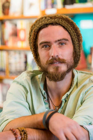 Handsome young man with knit cap in book store or library Standard-Bild - 120888018