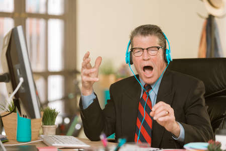 Professional man in a creative office singing at his desk Standard-Bild - 120888025