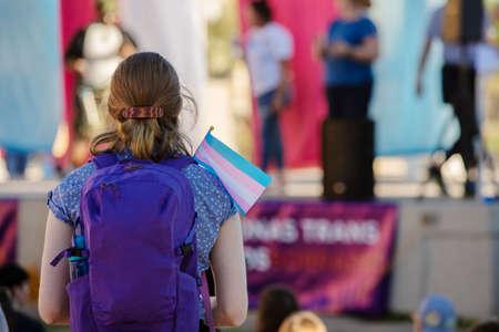 Mujer joven con mochila y bandera de apoyo trans en un mitin