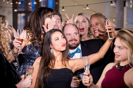 Pretty woman taking a selfie with friends at a party Standard-Bild - 120887794