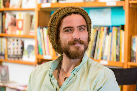 Attractive young man with knit cap in book store or library Standard-Bild - 120887796