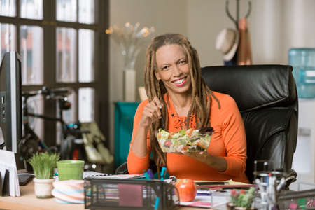 Stylish professional woman with dreadlocks having a healthy lunch in her office Standard-Bild - 120887807
