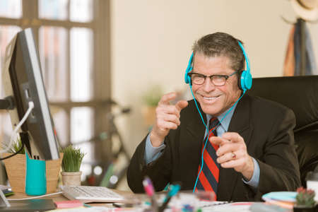 Professional man in a creative office listening to headphones and making a silly gesture Standard-Bild - 120887810
