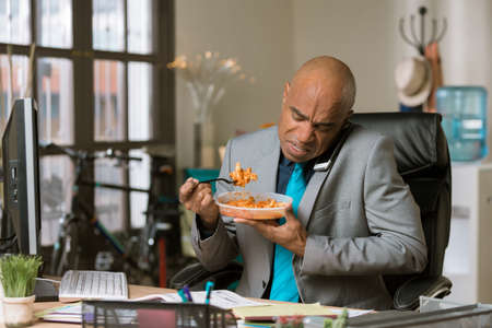 Professional man working through lunch eating packaged food Standard-Bild - 120887816