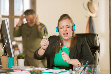 Young professional woman singing loudly enough to annoy a colleague Standard-Bild - 122101266
