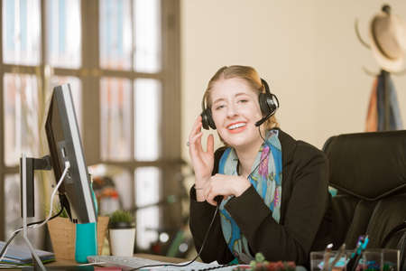 Young professional woman with braces on a headset call Standard-Bild - 122101271