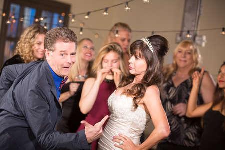 Bride Glares at Man Doing Funny Dance at a Wedding Standard-Bild - 122101277