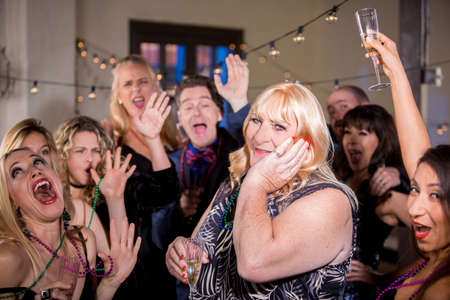 Trans woman at a party with enthusiastic friends